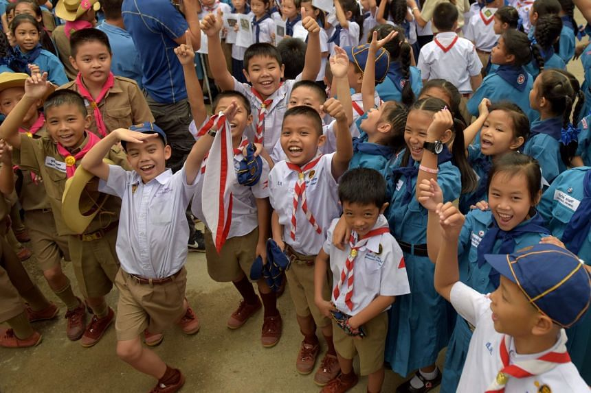 Thai students cheering at a school in front of the hospital where 12 boys and their coach were rescued after being trapped in a nearby cave for 18 days in Chiang Rai, on July 11, 2018.