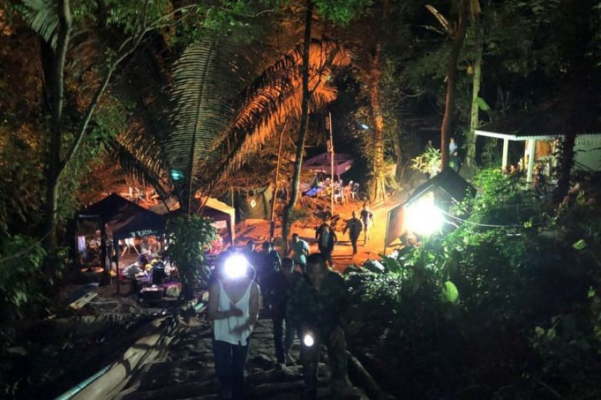 Rescue personnel walk at the site of the Tham Luang cave complex during rescue operations.
