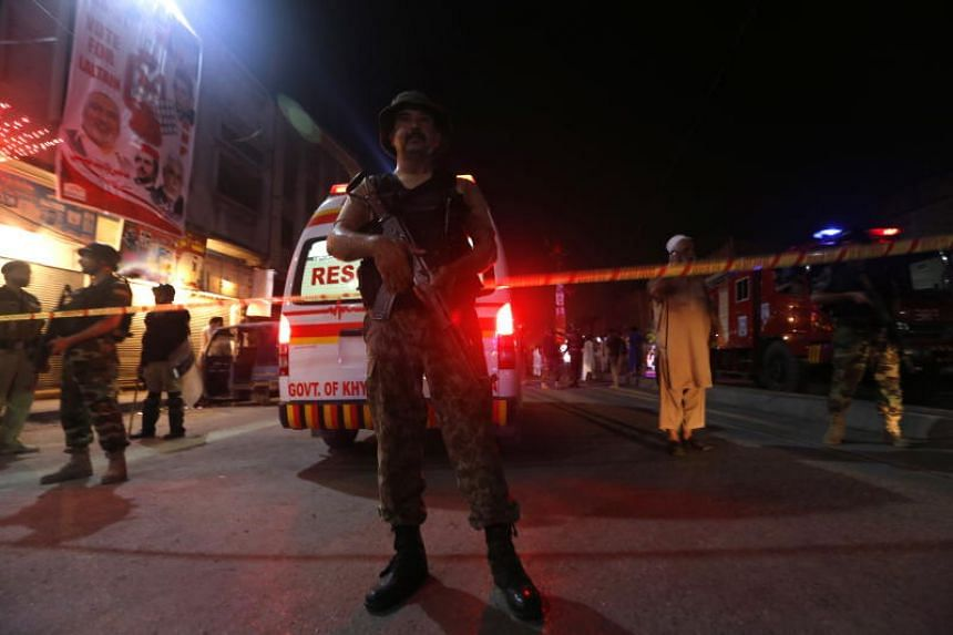 Pakistani security officials inspect the scene of a suicide bomb attack during an election campaign in Peshawar, Pakistan, on July 10, 2018.
