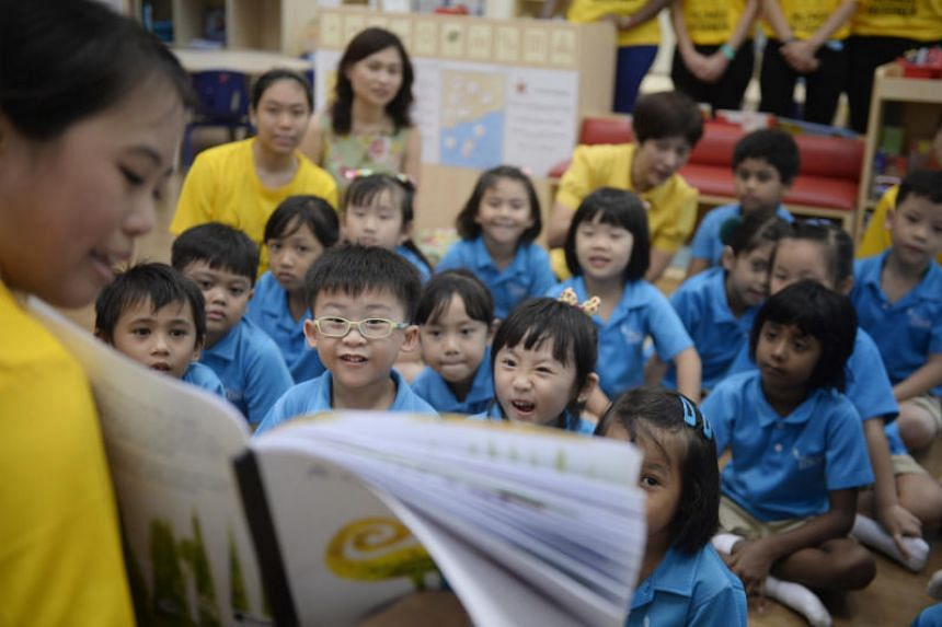 A Ngee Ann Polytechnic child psychology and early education student reading to children at the MOE kindergarten in Dazhong Primary School.