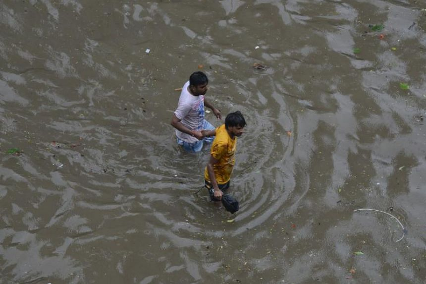 Indian men walk along a flooded street during heavy rain showers in Mumbai, on July 10, 2018.