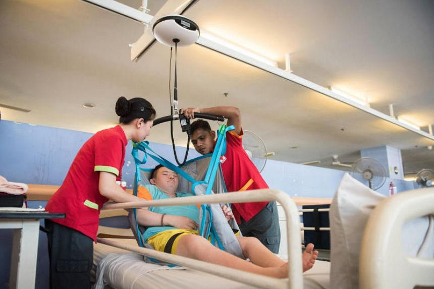 Healthcare aide Nalawayaa Suranga (right) and nursing aide Glaiza Minasalvas (left) hoisting a Red Cross Home resident Goh Quan Yao up with the ceiling hoist sling to get him from his bed onto the wheelchair.