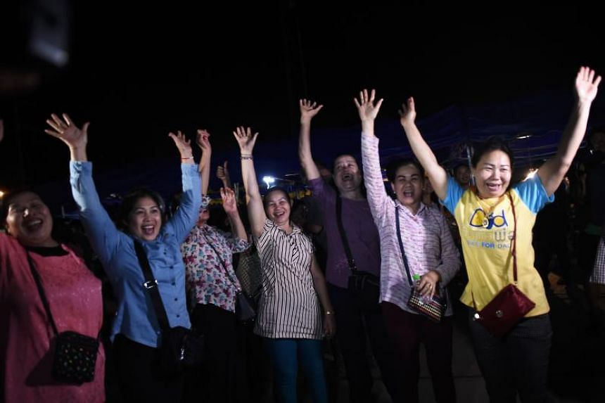 Volunteers celebrate at a makeshift press centre in Mae Sai district of Chiang Rai province on July 10, 2018, after the 12 boys and their football coach were rescued.