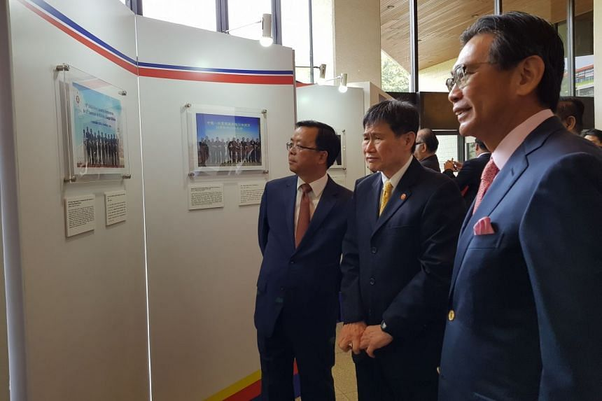 """China's Ambassador to Asean Huang Xilian (left), Asean Secretary General Lim Jock Hoi (centre) and Singapore Permanent Representative to Asean Tan Hung Seng (right) observe pictures displayed during a photo exhibition titled """"Living in Harmony"""" to c"""