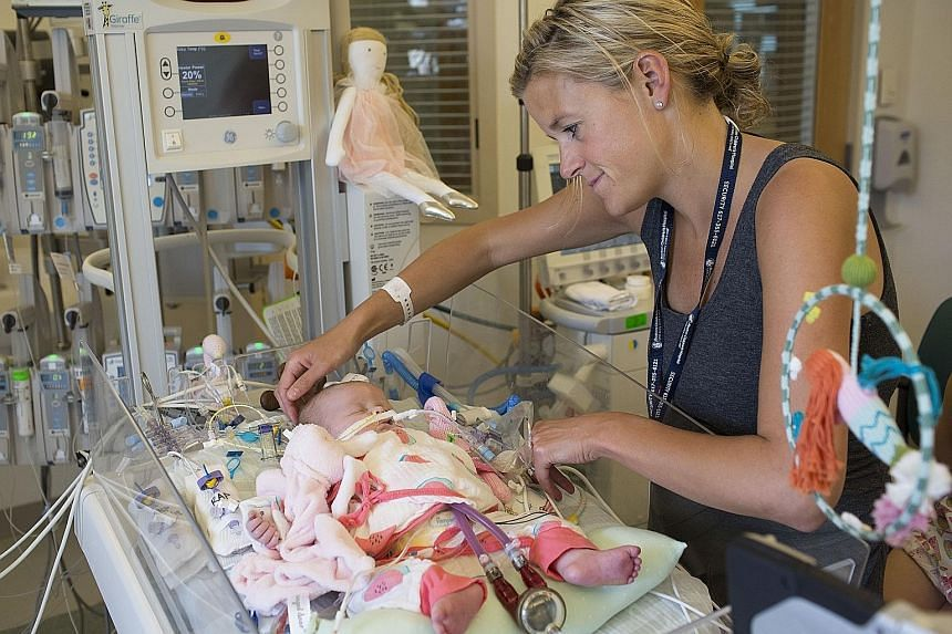 Ms Kate Bowen with her infant, Georgia, in the intensive care unit at Boston Children's Hospital last month. Georgia had had a heart attack, most likely while she was still in the womb, and her heart was profoundly damaged. Doctors tried to revive he