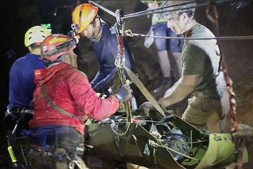 Rescuers at work in Tham Luang cave in Chiang Rai province. Hundreds of rescuers, including divers from around the world, helped to get the boys out.