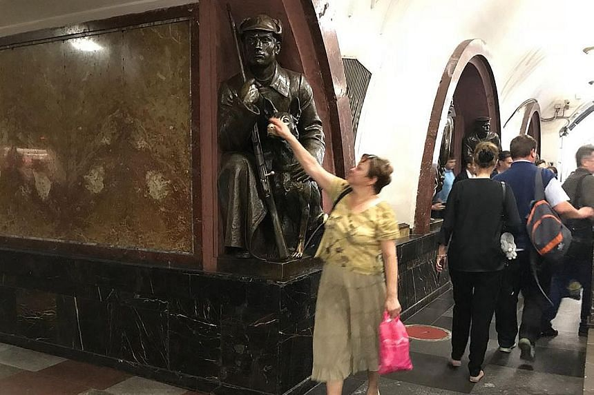 From far left: Mural at Park Pobedy, which features the world's fourth-deepest metro station at 84m underground. Komsomolskaya station has rich decoration devoted to the Soviet victory in the Great Patriotic War. A woman rubbing the nose of the dog b