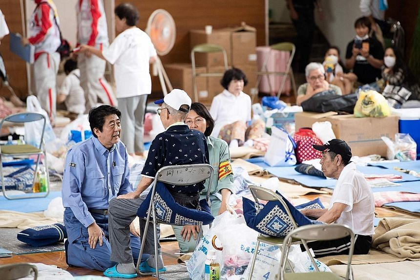Japan's Prime Minister Shinzo Abe yesterday visited a centre for people displaced by the recent flooding in Mabi, Okayama prefecture.