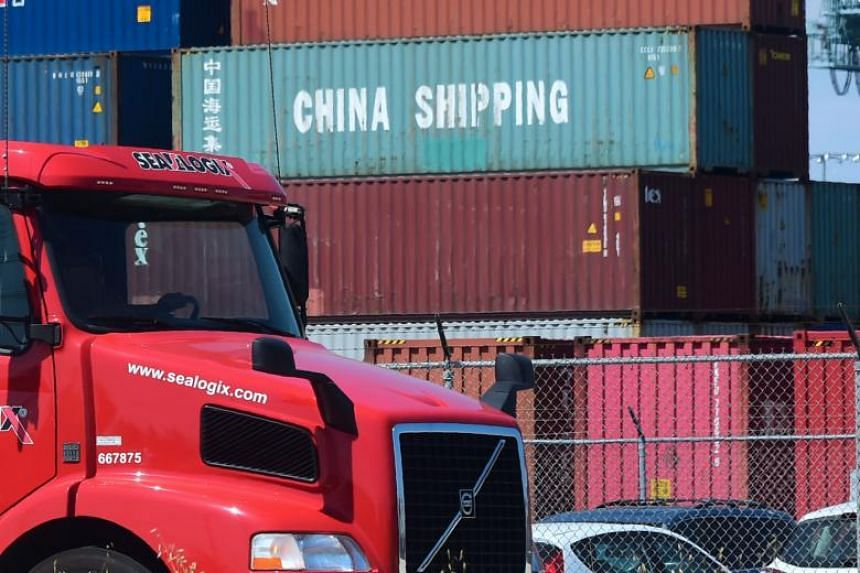 A container delivery truck drives past stacked piles of shipping containers at the Port of Long Beach in Long Beach, California, including one from China Shipping, a conglomerate under the direct administration of China's State Council, on July 6, 20