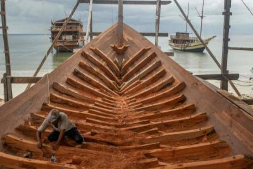A shipbuilder works on a traditional Pinisi boat in Tana Beru, on Indonesia's South Sulawesi island.