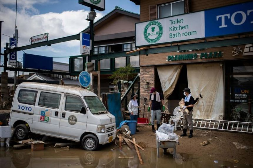 People cleaning up the damage in a flood-hit area in Mabi, Okayama prefecture, on July 10, 2018.