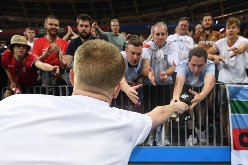 England goalkeeper Jordan Pickford hands his gloves to fans after the 2018 World Cup semi-final football match between Croatia and England in Moscow, Russia, on July 11, July 2018.