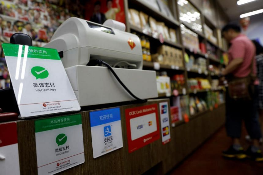 A WeChat Pay sign (left) on display at a shop in Singapore, on May 22, 2018.