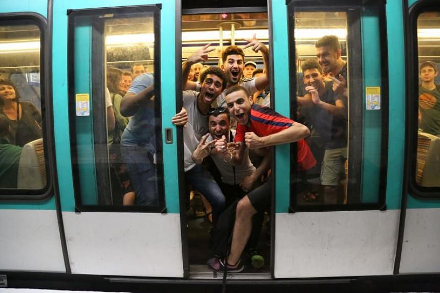 People celebrate France's 1-0 victory on board the Metro in Paris on July 10, 2018, after the final whistle of the Russia 2018 World Cup semi-final football match between France and Belgium.