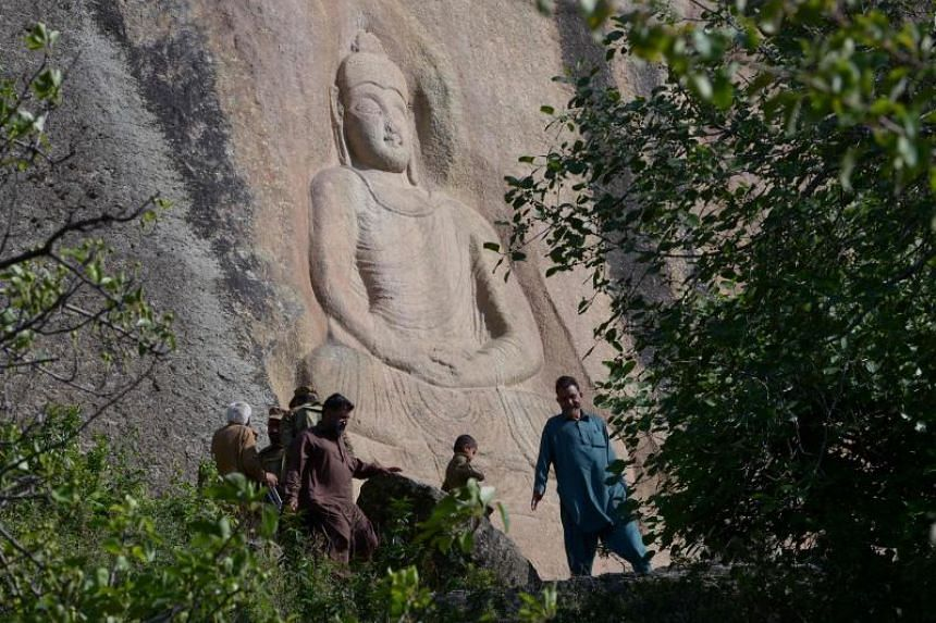 The Buddha of Swat, carved into a mountain in Jahanabad town in the Swat Valley of Pakistan, is seen on April 26, 2018, following a restoration process conducted by Italian archaeologists after the Taleban defaced it in 2007.
