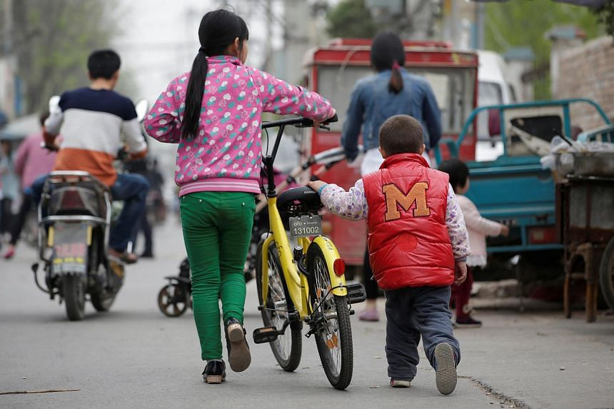 Children use an Ofo bike in a village on the outskirts of Beijing, China.