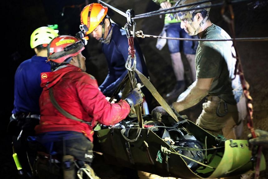 Rescuers holding an evacuated football team member during the ongoing rescue operations for the youth football team and their coach inside a cave complex at Tham Luang cave in Khun Nam Nang Non Forest Park, Chiang Rai province, Thailand.