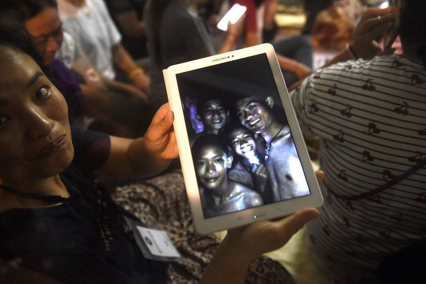 Thanaporn Promthep, mother of one of the 12 boys who went missing in a Thai cave, shows a photo believed to have been taken in 2017 of her son Duangpetch Promthep, (second right with light) and his coach Ekkapol Chantawong (right).