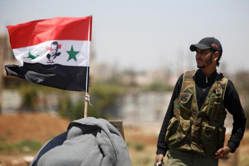 A Syrian army soldier stands next to a Syrian flag in Umm al-Mayazen, in the countryside of Deraa.