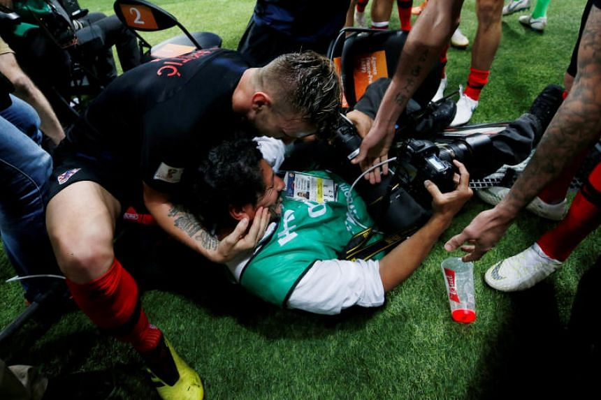 Croatia's Ivan Rakitic celebrates with AFP photographer Yuri Cortez after Mario Mandzukic scores their second goal during the World Cup semi-final match against England on July 11, 2018.