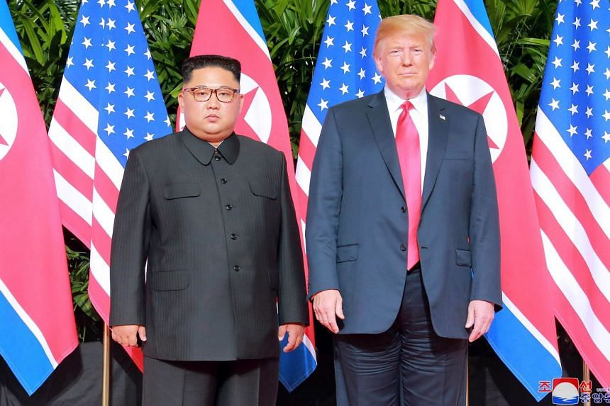 US President Donald Trump and North Korean leader Kim Jong Un pose at the Capella Hotel on Sentosa island in Singapore in this picture released on June 12, 2018.