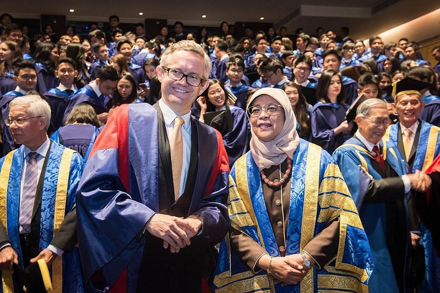 President Halimah Yacob shares a photo with Professor Simon Chesterman, dean of NUS Faculty of Law. About 360 law graduates were conferred their degrees at the ceremony yesterday. The ceremony was Madam Halimah's first since she became the university