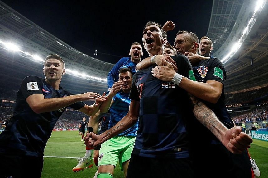 Left: Croatia's Mario Mandzukic celebrates with team-mates after scoring their second goal in extra time which sealed a 2-1 win over England at the Luzhniki Stadium in Moscow. Below: Croatian midfielder Ivan Perisic outjumps England's Kyle Walker to