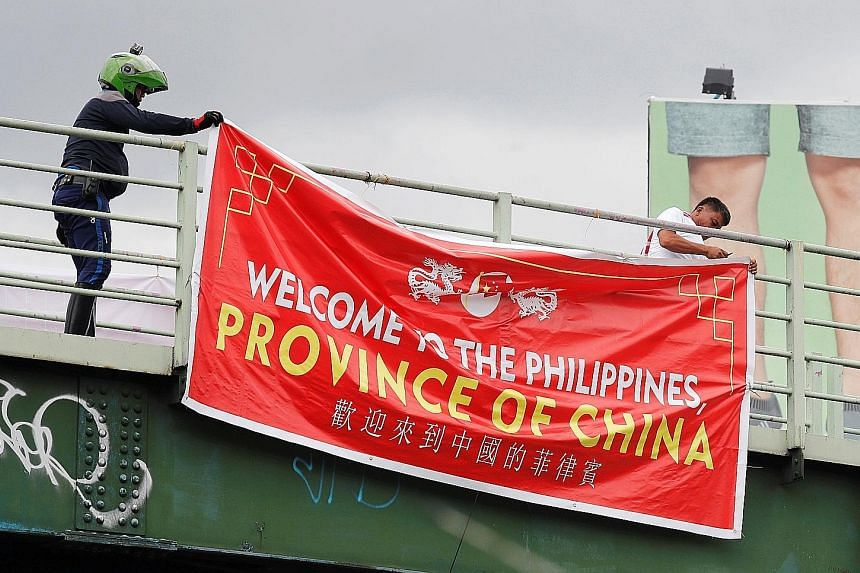 Traffic enforcers removing a banner hanging on an overpass in Taguig, Metro Manila, yesterday.