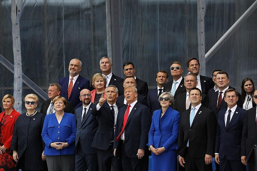 Nato secretary-general Jens Stoltenberg standing beside US President Donald Trump as they and other leaders watch a military aerial display at the Nato summit in Brussels, Belgium, on Wednesday.