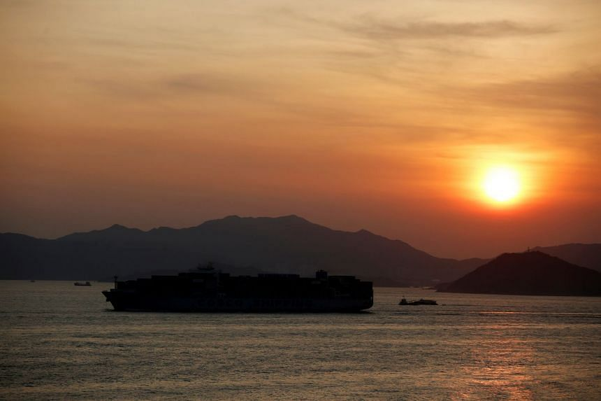 A container ship sails at sunset in Hong Kong. A rule to combat the merchant fleet's emissions of sulfur oxides starting in January 2020 could slow down ships in a few years.