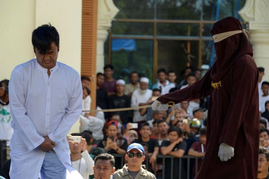 A man accused of having gay sex is whipped during a public caning ceremony outside a mosque in Banda Aceh, Indonesia, on July 13, 2018.