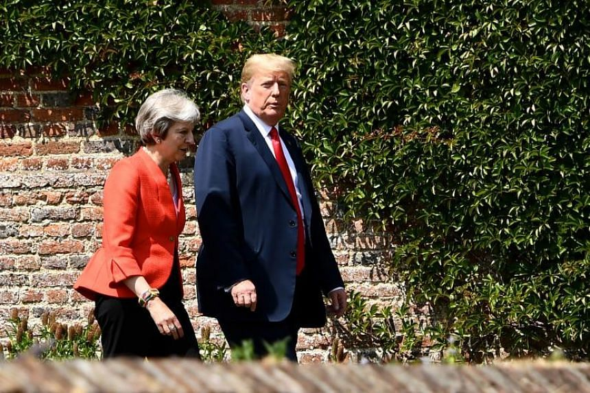 US President Donald Trump and British Prime Minister Theresa May walk to hold a joint press conference following their meeting at Chequers, the Prime Minister's country residence, on July 13, 2018.