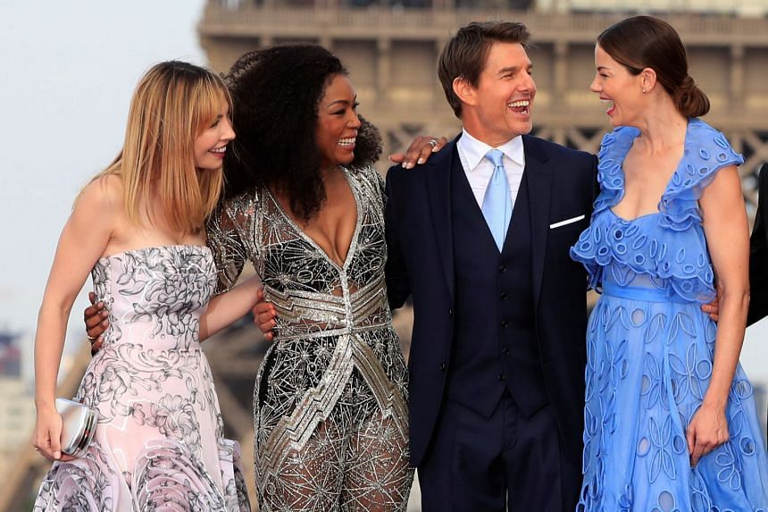 From left: Cast members Alix Benezech, Angela Bassett, Tom Cruise and Michelle Monaghan posing before the Eiffel Tower, on July 12, 2018.