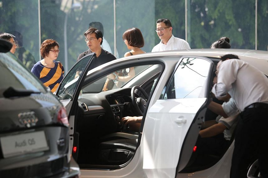 File photo showing buyers examining cars. More certificates of entitlement will be available for the next three-month quota period starting from August.