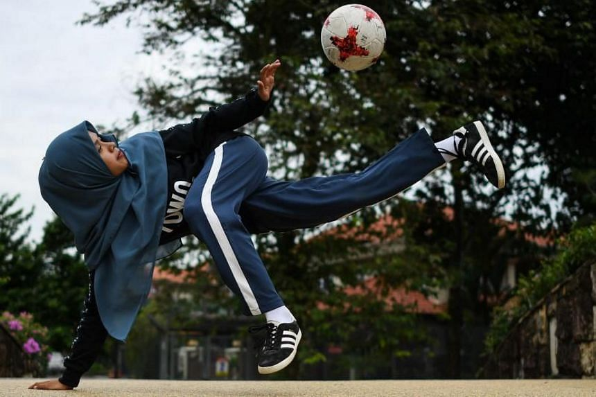 Female football freestyler Qhouirunnisa' Endang Wahyudi, 18, juggles the ball at a park in Klang, on the outskirts of Kuala Lumpur.