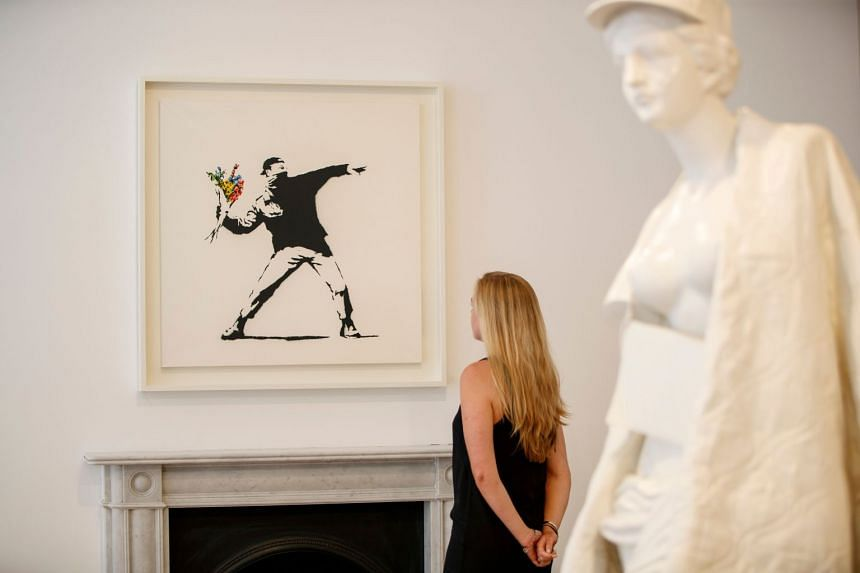 A gallery assistant poses with Banksy's 2006 artwork, Flower Thrower, which will be showcased at the London exhibition.