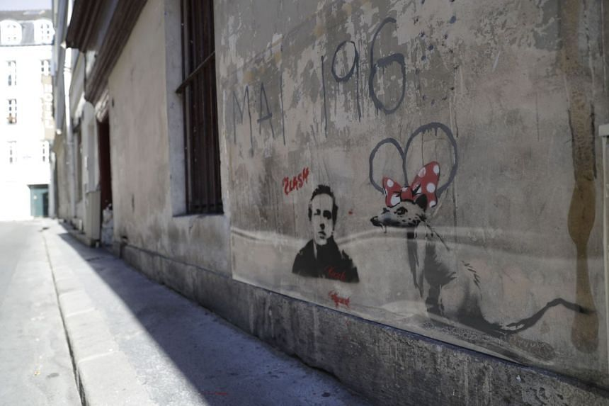 Banksy's recent protected artwork of a rat wearing a bow tie in Paris, on June 28, 2018. The identity of the street artist remains anonymous till today.