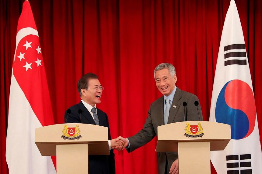 South Korea's President Moon Jae-in (left) shaking hands with Prime Minister Lee Hsien Loong after a joint press conference at the Istana presidential palace in Singapore, on July 12, 2018.