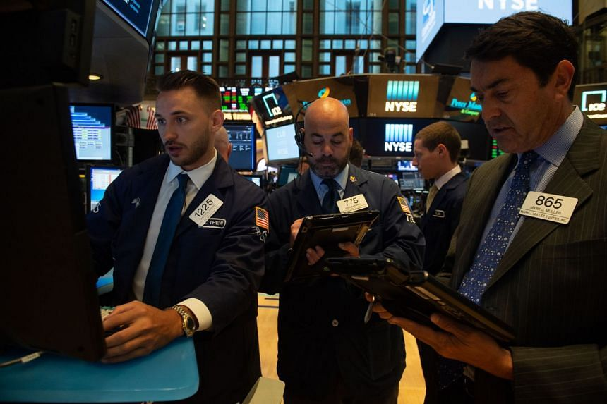 Traders work on the floor at the opening bell of the Dow Industrial Average at the New York Stock Exchange in New York, on July 10, 2018.