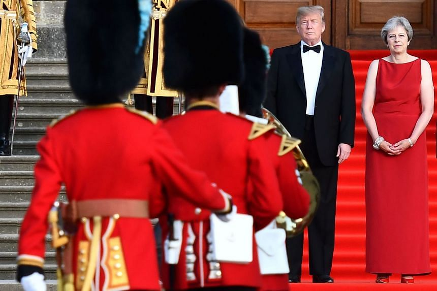 US President Donald Trump (left) and Britain's Prime Minister Theresa May stand on steps in the Great Court as the bands of the Scots, Irish and Welsh Guards perform a ceremonial welcome as they arrive for a black-tie dinner with business leaders at