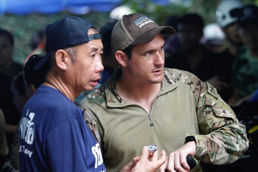 A US Special Operations Command Pacific Search and Rescue Team member (right) with a Thai Navy personnel. The 30-strong US team recommended that each child be confined in a flexible plastic cocoon called a Sked.