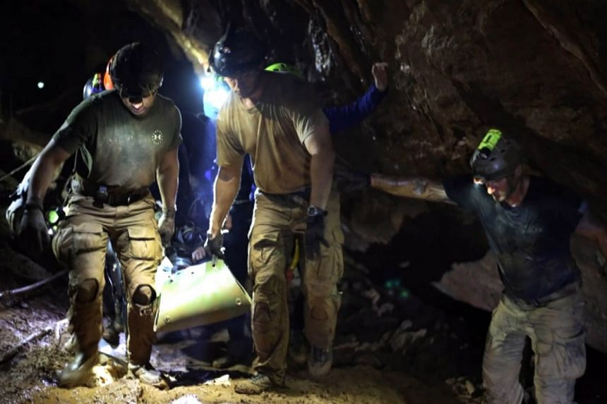 Rescuers carrying one of the boys inside Tham Luang cave during the rescue operation, in a handout photo from the Thai navy Seals.