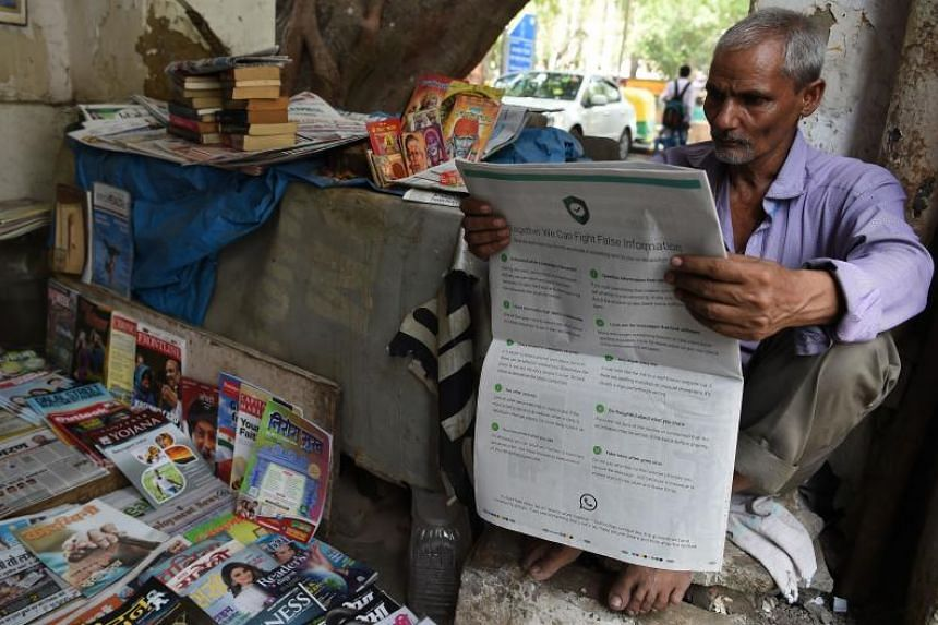 A photo illustration shows an Indian newspaper vendor reading a newspaper with a full back page advertisement from WhatsApp intended to counter fake information in New Delhi on July 10, 2018.
