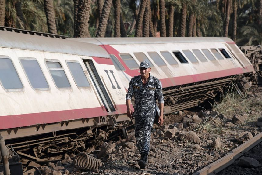 A police officer walks next to a passenger train which derailed in Egypt.
