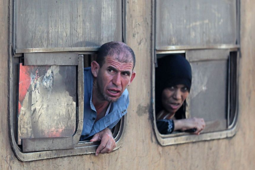 People look out of the windows of a train passing by the train which derailed in Egypt.