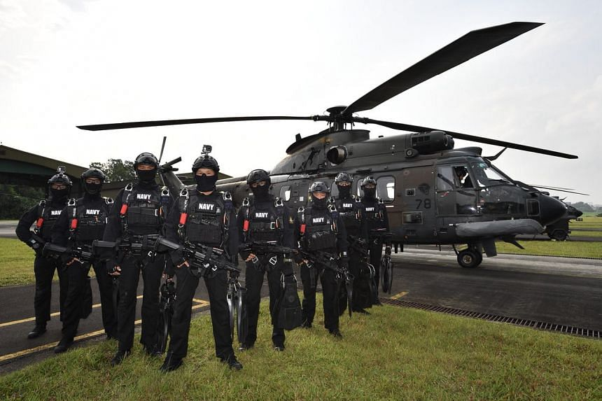 Naval combat divers pose for a photo in front of the Super Puma helicopter.
