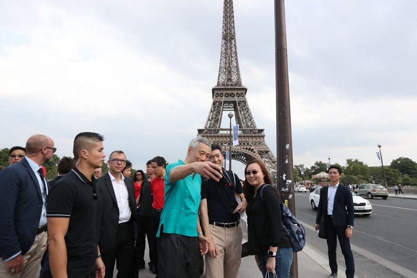 Prime Minister Lee Hsien Loong takes a wefie with a Singaporean couple in front of the Eiffel Tower.