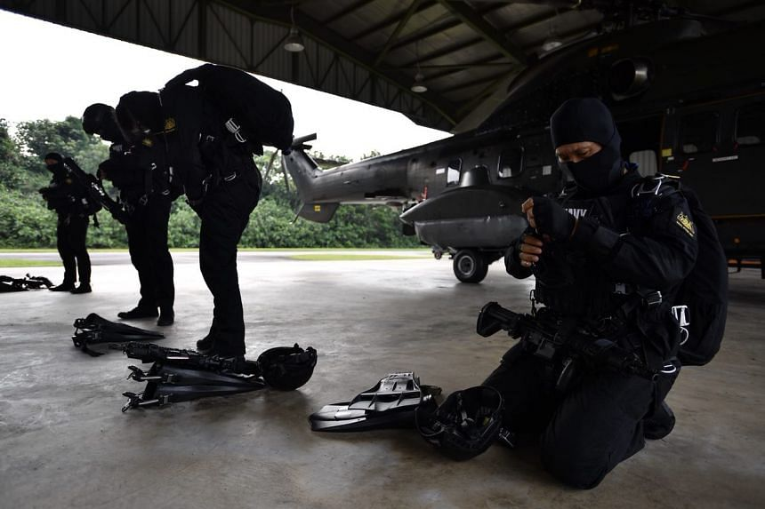 Naval combat divers gearing up for the free-fall water jump.