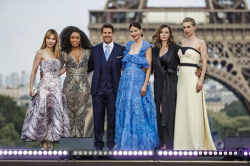 American actor Tom Cruise and his fellow Mission: Impossible - Fallout cast members (from far left) Alix Benezech, Angela Bassett, Michelle Monaghan, Rebecca Ferguson and Vanessa Kirby in front of the Eiffel Tower at the film's world premiere in Pari