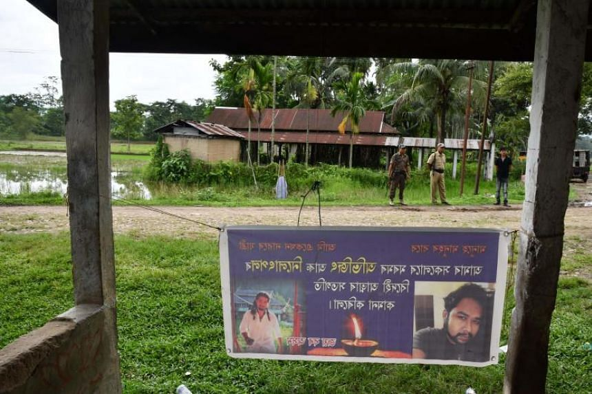 Indian security personnel stand near a commemorative poster for two men who were lynched nearby in Panjuri Kachari village.